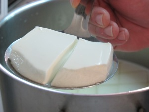 Curds being removed from whey.